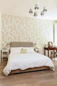 Double bed with upholstered headboard against floral wallpaper and antique dressing table a small distance away
