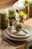 Serviettenring mit Weidenkätzchen auf Gedeck und grüne Kerzen neben Osterdeko