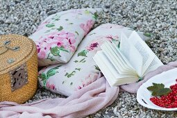 Cushions with a floral pattern, a blanket, a book and a picnic basket on a gravelly surface