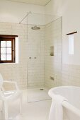 Partially visible white Ghost chair and bathtub in front of floor-level shower with glass partition in bathroom with white wall tiles