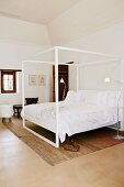 Canopied bed with white metal frame and white bed linen in simple bedroom with pale brown rug on lino-style floor