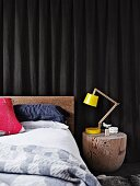 Yellow, designer desk lamp next to bed on smoothed section of tree trunk used as bedside table