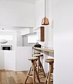 Modern, converted split-level area with solid balustrade; breakfast bar, wooden bar stools and copper pendant lamp in foreground