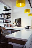 Open-plan interior with desk and adjoining kitchen counter below yellow pendant lamps