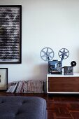 Old film projector decorating sideboard and modern artwork on wall