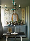 Chandelier above table in front of collection of goblets on farmhouse sideboard; framed floral pictures on wall