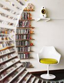 View through semicircular aperture of white, tulip chair by Eero Saarinen next to extensive CD collection on narrow shelves