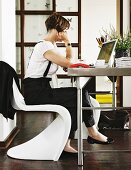 Woman sitting on white Panton chair working on laptop