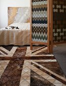 Geometric patchwork patterns in bedroom on leather rug and wall hanging behind double bed; screen with stylised woven pattern in between