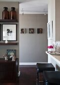 Kitchen counter, black leather stools and horses-head ornaments on sideboard