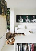 Wohnzimmer mit weissem Ledersofa und modernen Kunstwerken an den Wänden