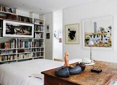 Rustikaler Tisch vor Doppelbett und Bücherregal, davor gerahmtes Bild in modernem Ambiente
