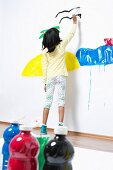 Girl painting the sea and an island on a wall in coloured paint