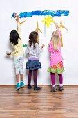 Three girls painting windmills, sun & sky on wall