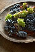 Weisse und blaue Weintrauben auf Holzschale