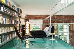 Loft apartment with steel girders and brick walls; leather armchair in front of bookcase on gallery bedroom with glass floor