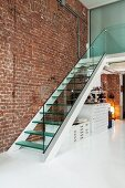 Staircase with glass balustrade and glass steps against exposed brick wall in designer loft apartment with white floor; map cabinets below stairs