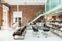 Designer loft apartment with steel and leather chairs at glass table between bookcase and retro armchairs; staircase leading to gallery with chilly glass balustrade in background against brick wall
