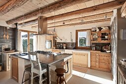 Island counter and vintage kitchen chairs in rustic fitted kitchen of wooden chalet