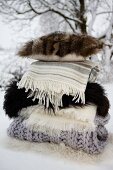Stacked woollen blankets, furs and fur-covered cushion in snow