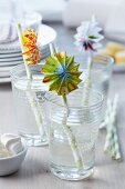 Colourful paper rosettes on drinking straws in glasses