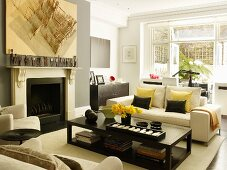 Pale sofa set and dark, box-shaped coffee table in elegant interior with wooden model suspended on wall and figurines on mantelpiece