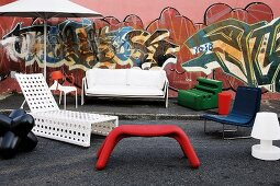 Stylish chairs, sofa, lounger and parasol for the garden and terrace in front of house wall painted with graffiti