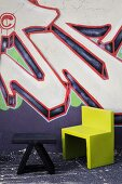 Small, low, black table and green chair in front of house wall painted with graffito