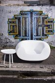 White chair and side table in front of house wall painted with graffito