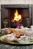 Traditional china tea service and Christmas pastries on tray with open fire in background
