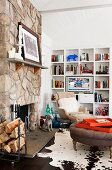 Seating area with armchair, ottoman, cowhide rug and white fitted shelves in front of rustic, stone chimney breast