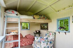 Loft bed and ladder in romantically furnished shepherd's hut