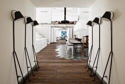 Retro, black standard lamps against walls in corridor of loft apartment