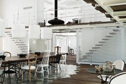 Dining table and various chairs on tiled floor area in front of staircase with white perforated lattice below mezzanine