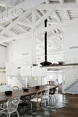 Dining table with various chairs on tiled floor area and pendant lamps with white fabric lamps in front of mezzanine in roof with whitewashed roof structure