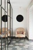 Antique armchair on tiled floor in various shades of grey next to partition made from old mirrored panels