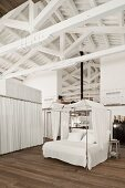 Four-poster bed with white fabric canopy in sleeping area below white roof beams of loft apartment
