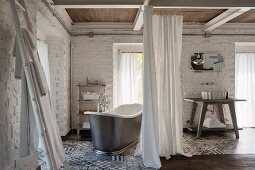 Free-standing vintage bathtub and washstand screened by curtains, whitewashed brick walls and grey and white patterned tiled floor