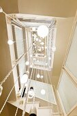 View up square stairwell with light sculpture made from various pendant lamps suspended from ceiling