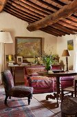 Living room in rustic, cosy country-house style with patterned armchair and artistic ambiance