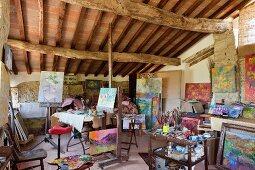 Colourful artworks in studio below rustic ceiling in Mediterranean holiday home