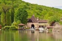 Blick über kleinen See auf eine französische Mühle aus dem 17. Jahrhundert; Hügellandschaft der Dordogne im Hintergrund