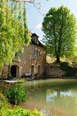 Teich vor historischem Mühlengebäude in der Dordogne