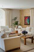 Sitzgruppe mit hellen Polstersofas und Holztisch im Wohnzimmer; bunte Malerei an Natursteinwand im Hintergrund