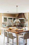 Wohnküche mit verglasten, Türfronten; im Vordergrund gedeckter Thekentisch mit Hängeleuchte im Industriestil