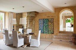 Eleganter Essplatz mit Hussenstühlen und Stehleuchten vor Glastrennwand und Treppe; Triptychon auf Natursteinwand und Blick durch historischen Rundbogen