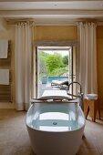 Freistehende Badewanne mit Holzablage; im Hintergrund offene Terrassentür mit Blick auf den Pool