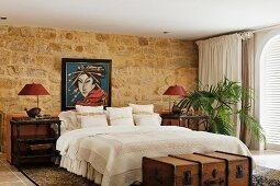 Gemütliches Schlafzimmer mit exotischem Flair durch Überseekoffer, Tischchen im Kolonialstil und asiatischem Portrait über dem gemütlichen Doppelbett