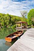 Ruderboot an einem Holzsteg mit Pavillon; bewaldeter Hügel im Hintergrund