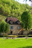 Idyllisch gelegenes Mühlengebäude mit Teich vor bewaldetem Hügel in der Dordogne